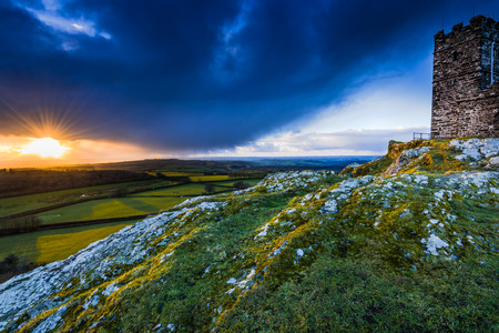 farmlands: 13th Century Church in Brentor, England on hill top. View over farmlands and coutryside at sunset with long shadows and stormy clouds, dramatic sky.