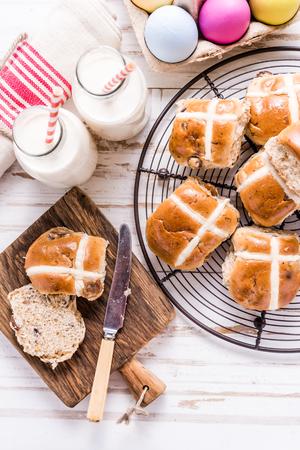 Easter traditional breakfast, hot cross bun and Easter eggs. Bright colors, view from above on wooden table.