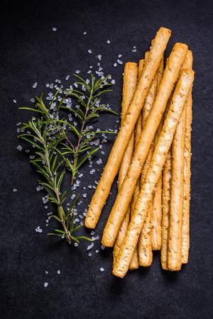 breadstick: Crispy breadsticks with salt and fresh rosemary on dark board. Stock Photo