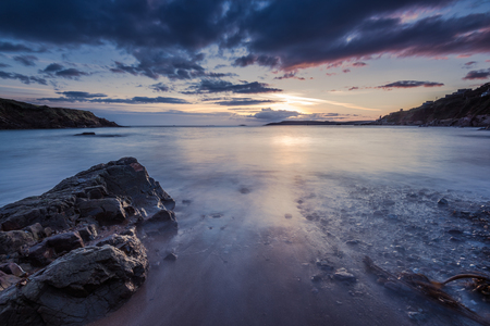 slow motion: Sunset at rocky beach with slow motion blur water. Pastel colors and tranquil feeling.
