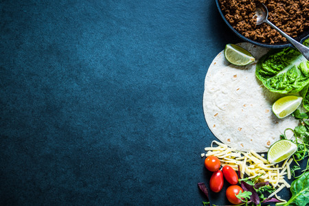 food dish: Mexican fajitas or tortillas, food border background with space for text or recipe. Overhead on dark slate.