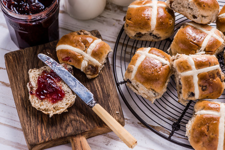 wooden cross: Easter breakfast with traditional hot cross bun and jam. From above on wooden table. Stock Photo