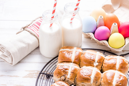 bollos: Hot cross bun on tray with Easter vibrant eggs and milk. Easter breakfast concept, view from overhead. Foto de archivo