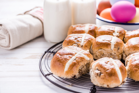 Hot cross bun on tray with Easter vibrant eggs and milk. Easter breakfast concept, view from overhead.
