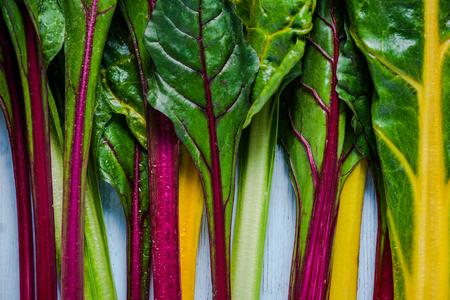 Levendige groente, zwitsers regenboog snijbiet, plat op houten tafel van overhead.