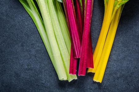 ensalada verde: acelga suiza arco iris, vibrante vegetal. aplanada, desde arriba en la pizarra oscura. Foto de archivo