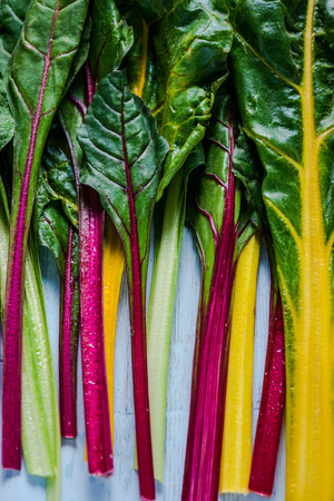 chard: Vibrant vegetable, swiss rainbow chard, flat lay on wooden table from overhead. Stock Photo