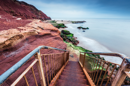 jurassic coast: Wild beach and red rock cliffs in famous heritage site Jurassic Coast in UK