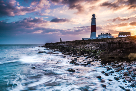 time lapse: Time lapse sunset on coast with lighthouse on cliffs in Portland, Dorset, UK. Stock Photo