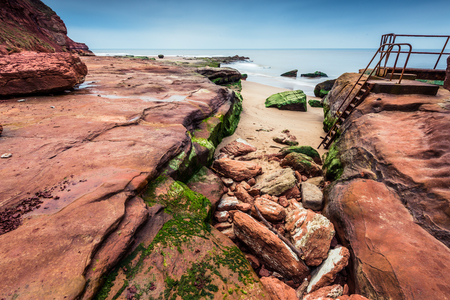jurassic: Wild beach and red rock cliffs in famous heritage site Jurassic Coast in UK