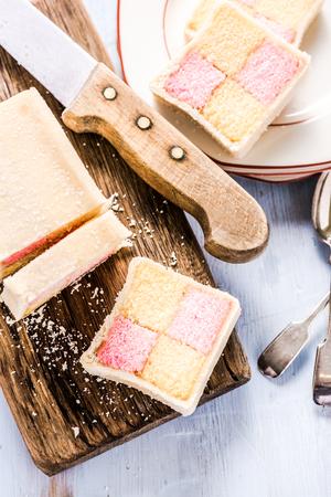 chequer: slicing Battenberg homemade sponge cake, on wooden board Stock Photo
