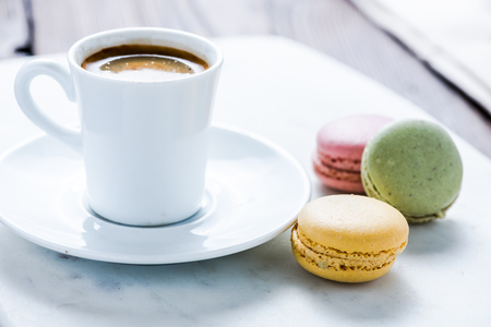 sweet treat: coffee cup and sweet treat macaroon, on wooden table