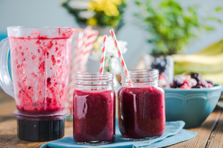 negative space: Freshly blended smoothie, in sunny kitchen on farmhouse table. Negative space for text, ingredients and fresh fruits in background.