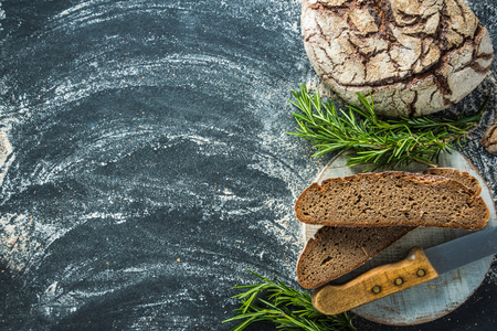 artisan bakery: sliced rye artisan bread loaf, on dark slate from above Stock Photo