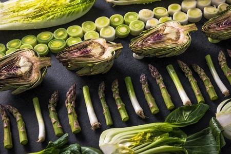 Green vegetables cut in halves, flat lay design on dark background, symmetric.