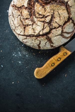 artisan bakery: Artisan whole grain rye bread, on dark slate. Ingredients border background