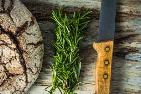artisan bakery: Artisan bread loaf, rosemary and knife, flat lay on wooden board