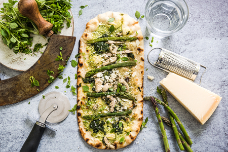 woodfired: Pizza with fresh spring vegetables and herbs, from overhead on slate background