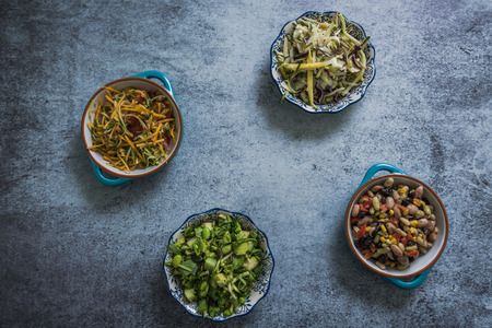 borlotti beans: assorted salads in bowls from above, on slate table with copy space for tect