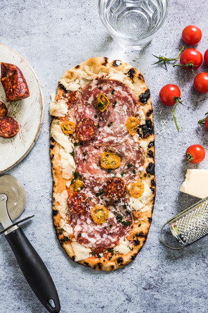 woodfired: Italian salami and tomatoes pizza, from above on slate
