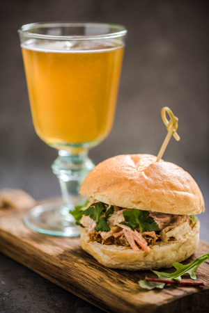 bap: serving pub food, pork bap with coleslaw, on wooden board with local artisan Ale Stock Photo