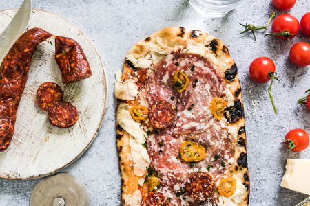 woodfired: artisan baked pizza with ingredients on slate background