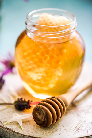 honey comb: jar with sweet honey and vax comb and wooden dipper, helathy clean eating Stock Photo