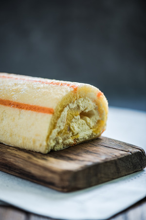 swiss roll: swiss roll with creme on wooden board Stock Photo