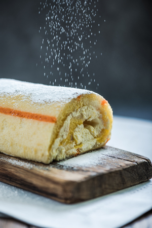 swiss roll: decorating swiss roll with sugar, food in action Stock Photo