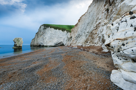jurassic: white cliffs and lonelly rock formation on the beach in Dorset Jurassic Coast