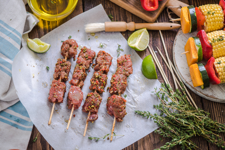 marinate: marinate beef skewers on wooden table for barbecue