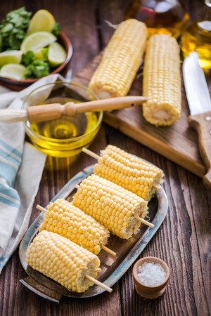 high angle shot of sweetcorn cob ready for bbq, on wooden table