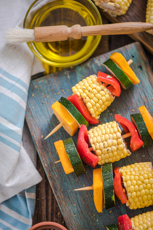 high angle shot: preparation for barbecue party, vegetable skewers on wooden table, high angle shot Stock Photo