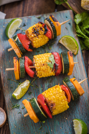 high angle: grilled vegetable skewers with fresh herbs on wooden board, high angle shot