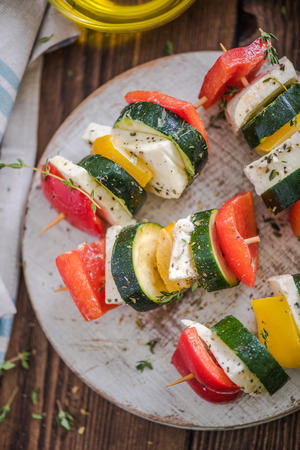 haloumi: healthy bbq, vegetable and haloumi cheese skewers, view from above on rustic wooden board