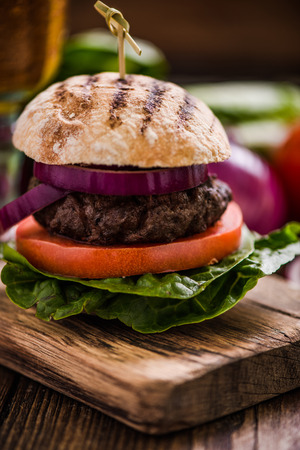 gastro: beef burger and vegetables ingredients on wooden rustic table