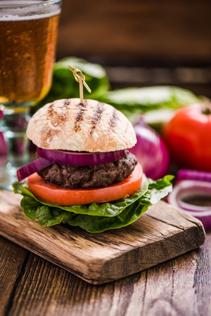 gastro: bbq burger with pint of lager on wooden table