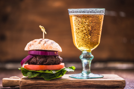 gastro: homemade burder with pint of lager on wooden board