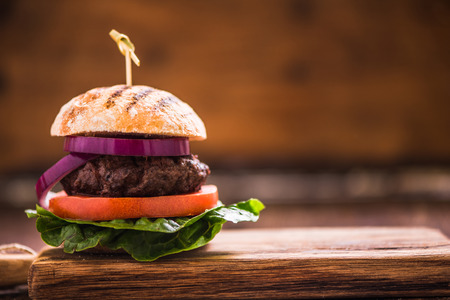 gastro: hambrger on wooden board with copy space wooden background