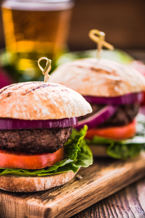 gastro: two burgers on wooden board and beer, pub background Stock Photo