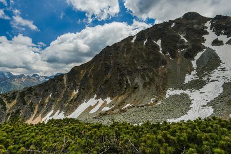 rocky peak: Snow patches on high rocky peak in Tatra range Poland, blue sky in background