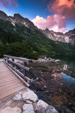 hing: wooden foot bridge in hing mountains over lake with dramatic sky at sunset Stock Photo