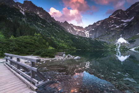 foot bridge: wooden foot bridge in hing mountains over lake with dramatic sky at sunset Stock Photo