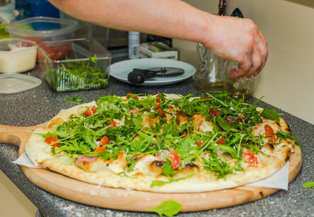 vegeterian: chef finish off vegeterian pizza with cheese