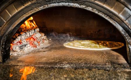 pizzadeeg in traditionele Italiaanse houtkachel Stockfoto