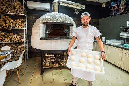 bebaarde chef-kok trots tonen pizzadeeg in het traditionele restaurant