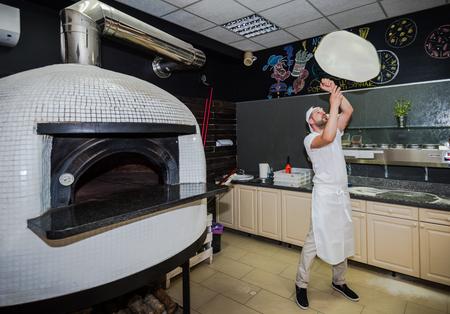 pizzaiolo Barbu jouer avec de la pâte à pizza dans le restaurant traditionnel