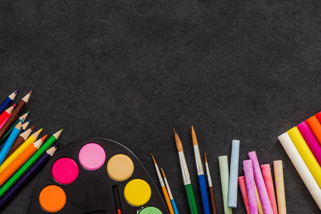 color pencil: art suppllies, pencils, paints, brushes and chalk on dark slate background