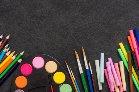 vibrant paintbrush: art suppllies, pencils, paints, brushes and chalk on dark slate background