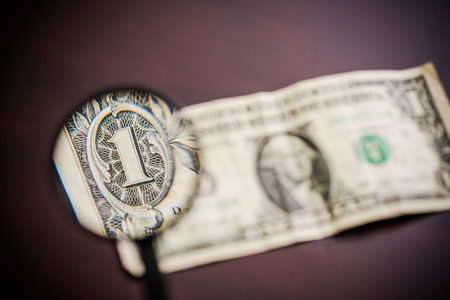 counterfeiting: magnified glass over dollar note, fraud and investigation concept